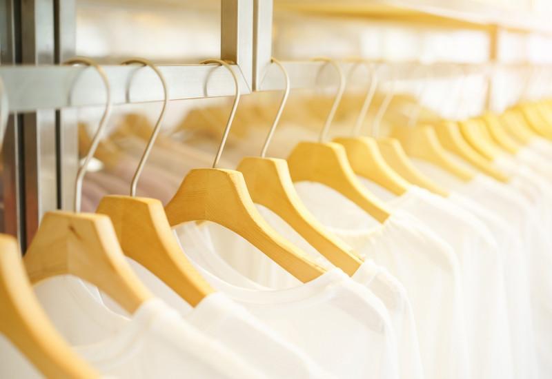 in einem Geschäft hängen viele weiße T-Shirts auf Bügeln an einer Stange