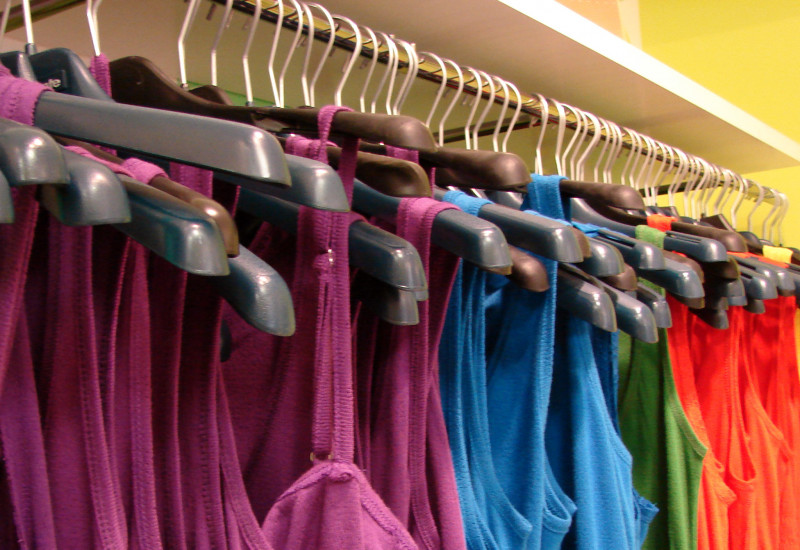 pink, blue, green, red and yellow tops hanging on clothes hangers in a shop