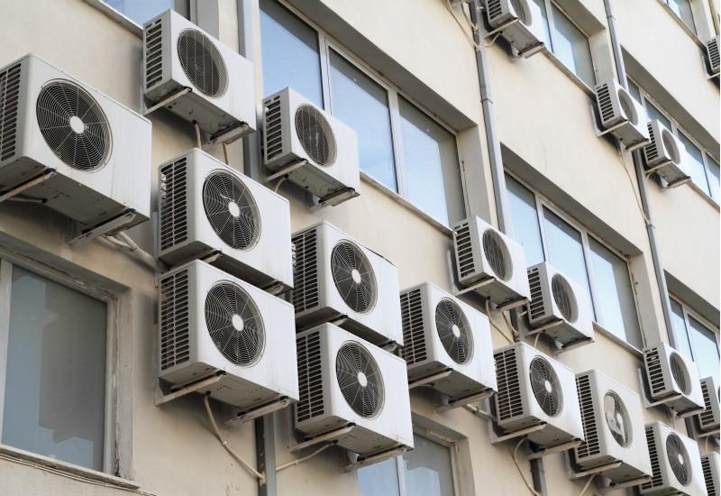 viele Klimaanlagen-Kästen an einer Hausfassade