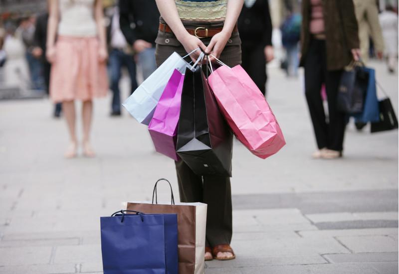 eine Frau steht in einer Fußgängerzone und hat viele Taschen von Einkäufen in Modegeschäften in der Hand und vor sich abgestellt