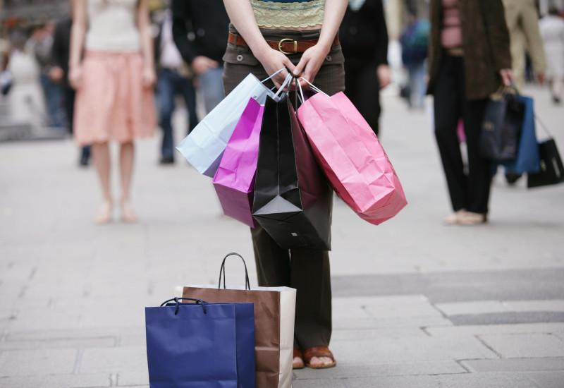 Frau mit 6 großen Papiertragetaschen in einer Fußgängerzone