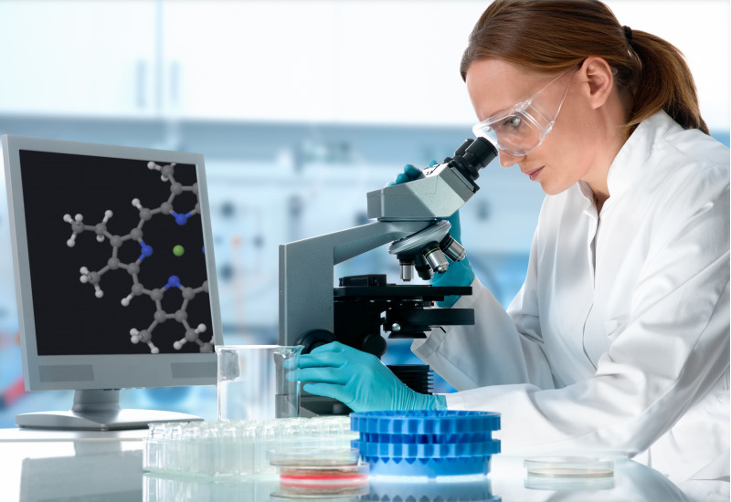 Frau in Laborkleidung schaut in ein Mikroskop, das Bild wird auf einen Monitor übertragen