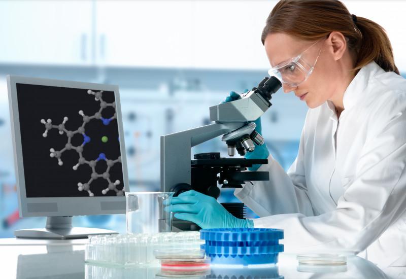 Wissenschaftlerin an einem Mikroskop