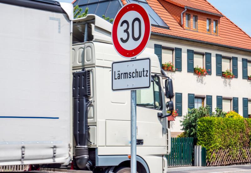 """Ein Lkw fährt durch ein Wohngebiet, an der Straße steht ein Verkehrsschild """"Tempo 30 Lärmschutz""""."""