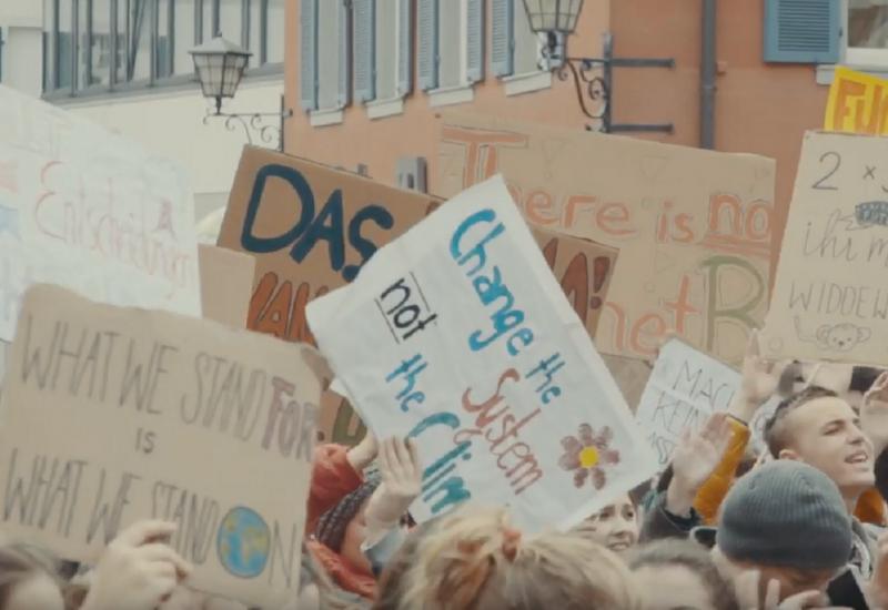 Jugendliche auf einer Demonstration halten Plakate für mehr Klimaschutz in die Luft