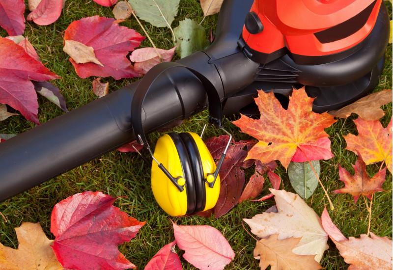 Auf einer Rasenfläche liegen ein Laubbläser, ein Gehörschutz-Kopfhörer und bunte Blätter.