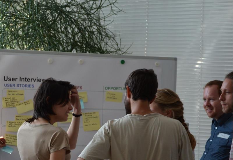 Teilnehmerinnen und Teilnehmer eines Workshops vor einem Flipchart