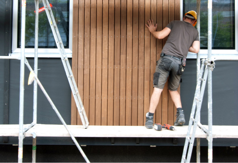 zwei Bauarbeiter stehen auf einem Baugerüst und montieren zusammen ein Holz-Fassadenelement