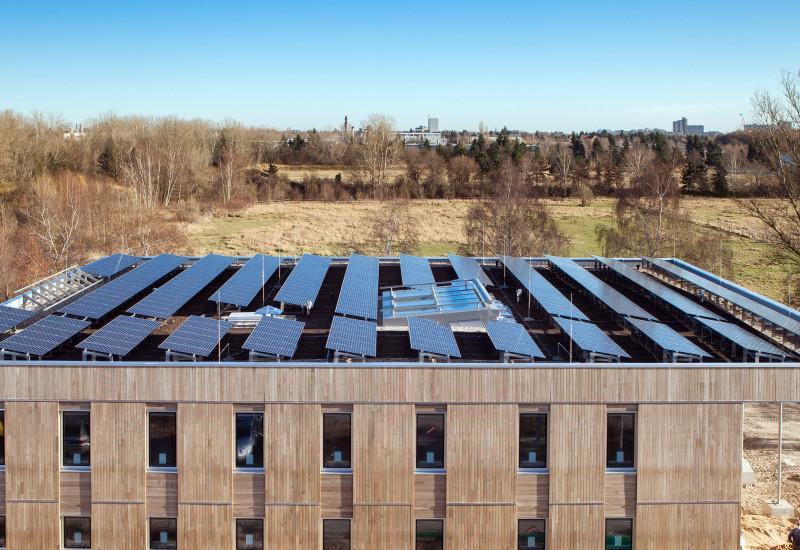 quadratischer zweigeschossiger Bau mit Holzfassade und Solarzellen auf dem Dach