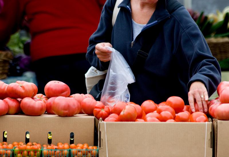 eine Kundin packt an einem Marktstand Tomaten in einen dünnen Plastikbeutel