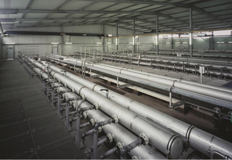 in einer Leichtbauhalle mit einem Boden aus Metallgittern steht eine große Anlage aus einem Rohrsystem
