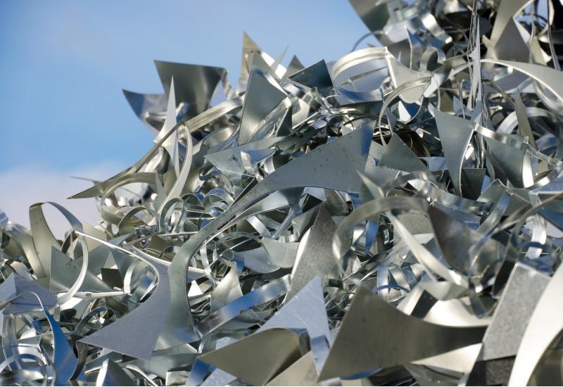 Verschnitt-Stücke aus silbernen Metallblechen liegen auf einem großen Haufen, dahinter ist blauer Himmel zu sehen