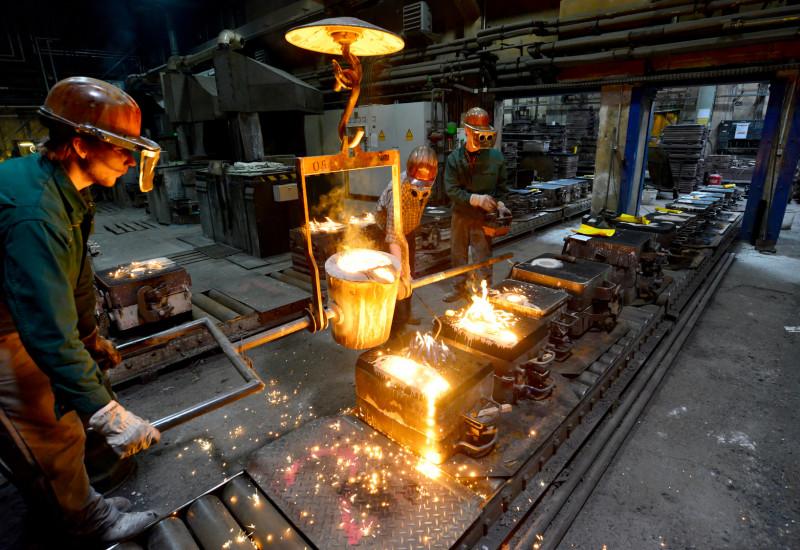 In einer Gießerei gießen Arbeiter flüssiges, glühendheißes Metall in Formen
