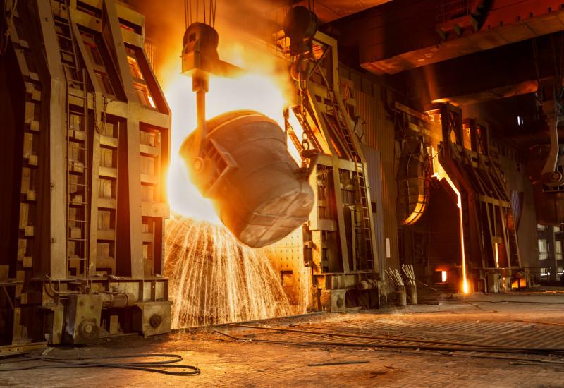 in einer Werkshalle wird ein riesiger Bottich mit glühendheißem, flüssigen Metall ausgekippt