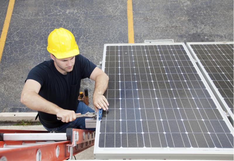 Arbeiter mit gelbem Schutzhelm arbeitet an einer Solaranlage