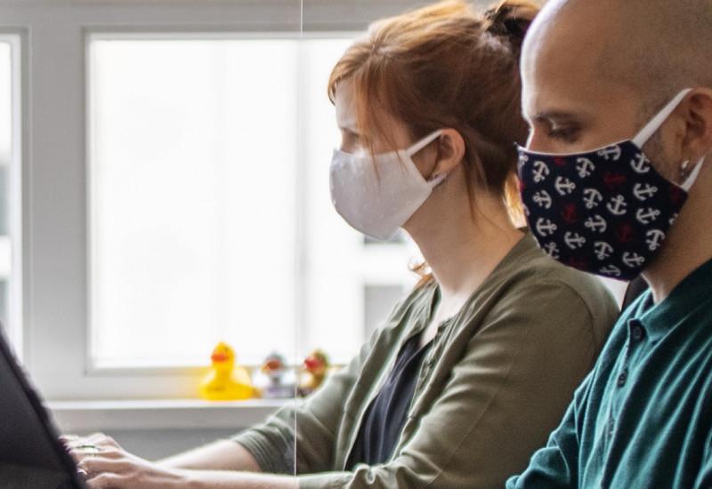 vier junge Erwachsene sitzen mit Alltagsmasken in einem Büro an Computern