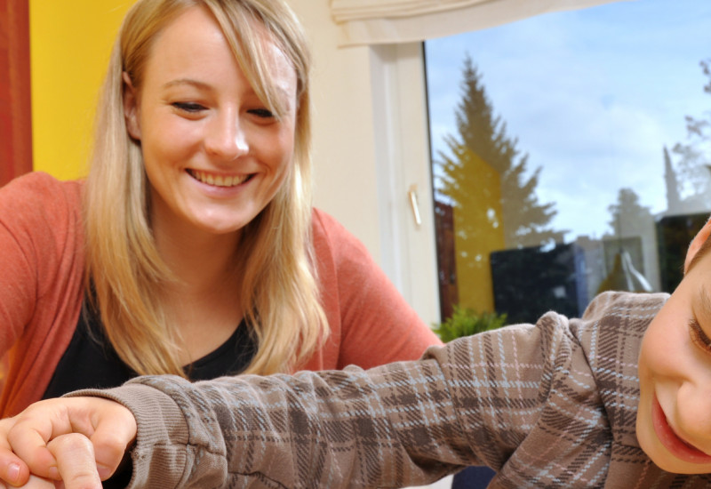 Mutter und Kind beim Memory-Spielen, die Mutter deckt ein Kärtchen mit einer Schlange auf, der Junge schaut neugierig unter die Karte, bevor sie ganz aufgedeckt ist
