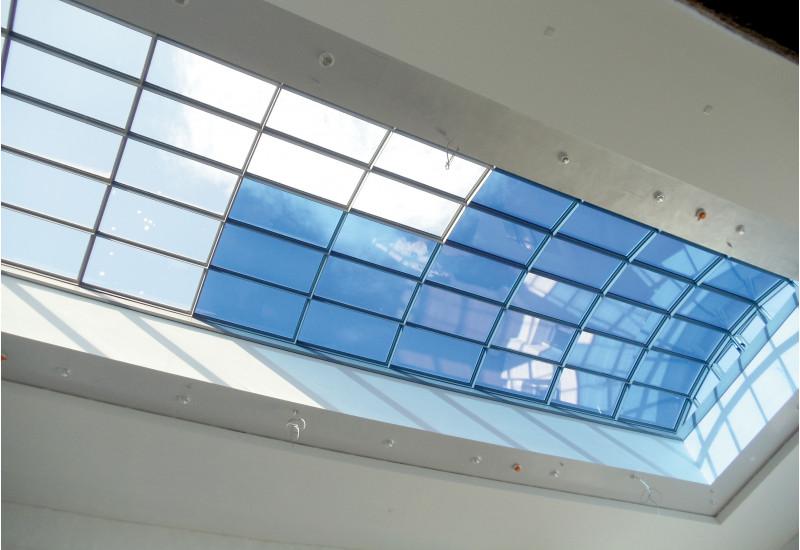 großes Dachflächenfenster aus vielen verschiedenen Glasflächen, einige sind durchsichtig, andere bläulich