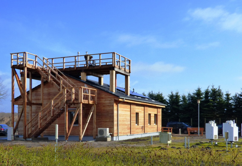 einstöckiges Holzhaus, eine Treppenanlage führt zu einer Plattform auf dem Dach