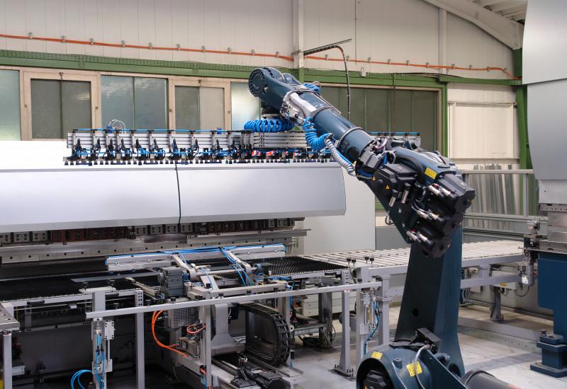 Fertigungshalle, in der ein großer Roboterarm arbeitet