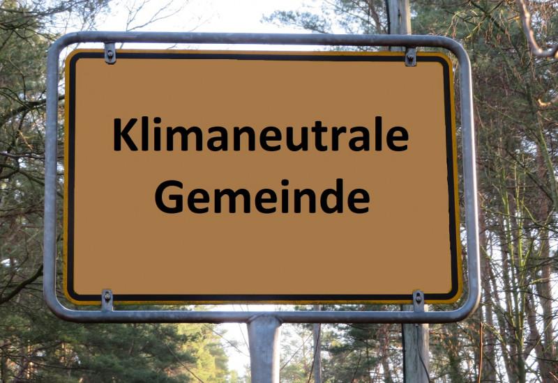 """auf einem Ortsschild steht """"Klimaneutrale Gemeinde"""""""
