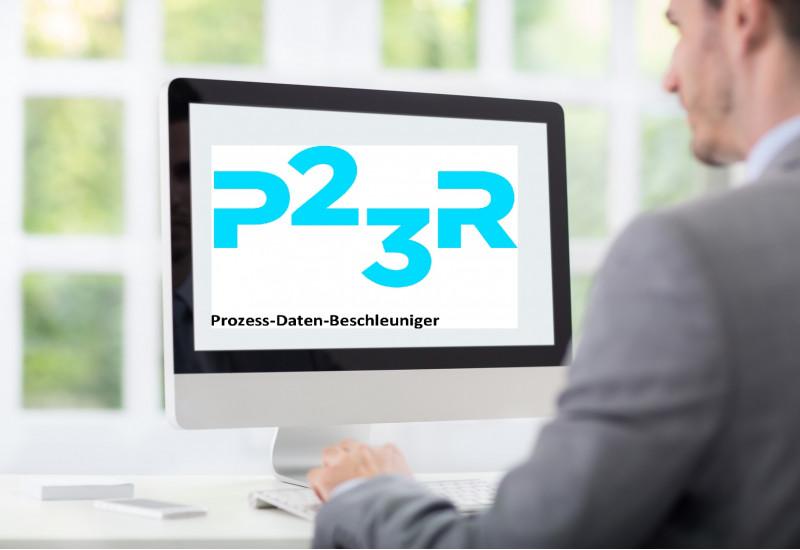 """ein junger Mann im Anzug sitzt im Büro an einem Schreibtisch. Auf dem Computermonitor steht """"P23R Prozess-Daten-Beschleuniger"""""""