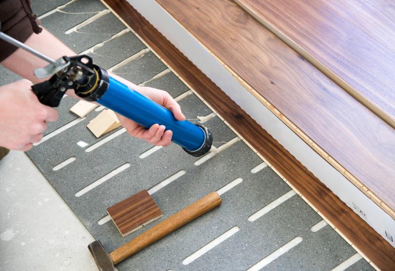 ein Fertigparkett oder -Laminat wird verlegt, dazu wird auf einer Trittschalldämmung ein Klebstoff aufgebracht