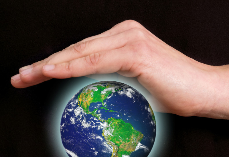 Person holding protective hands over and under a floating, bright globe