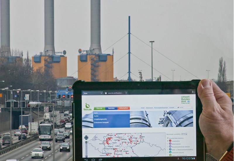 eine Hand hält ein Tablet mit dem Webangebot thru.de vor ein Kraftwerk hinter einer Stadtautobahn