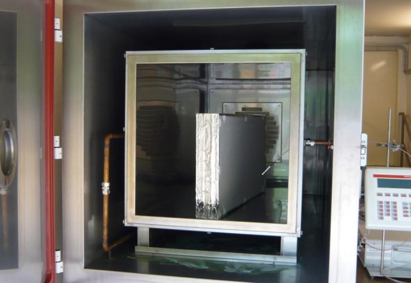 in einem großen Stahlbehälter mit Tür steht ein Bauprodukt, daneben ein elektronische Gerät zur Durchführung einer Emissionsmessung