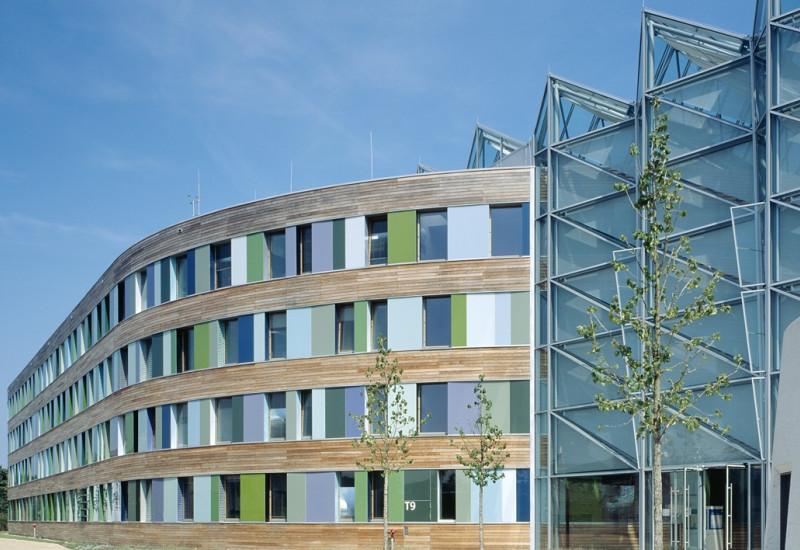 Gebäude des UBA in Dessau Roßlau: verglaster Eingangsbereich und Holzfassade mit bunten Glasscheiben in Grüntönen