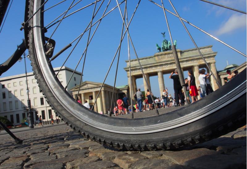 durch die Speichen eines Fahrradreifens ist das Brandenburger Tor in Berlin zu sehen
