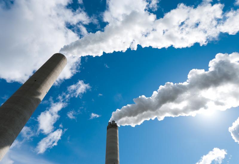 aus Industrieschornsteinen steigt Rauch in blauen Himmel auf