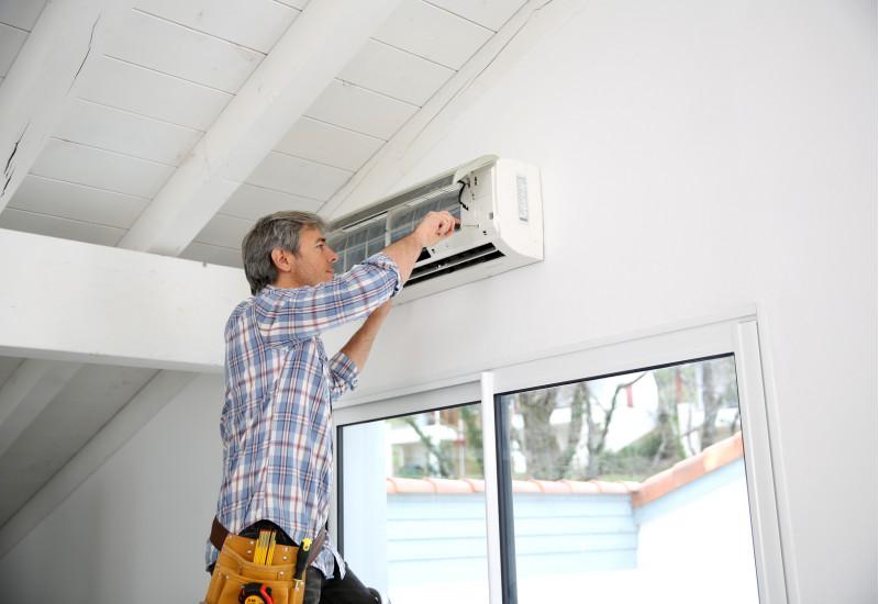 Mann schraubt an einem Raumklimagerät, dass in einem Haus über einer Terrassentür an der Wand angebracht ist