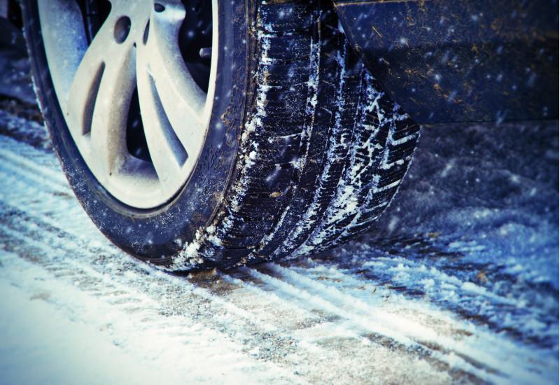 ein Auto fährt bei Schneetreiben über eine verschneite Fahrbahn, Großaufnahme eines Reifens