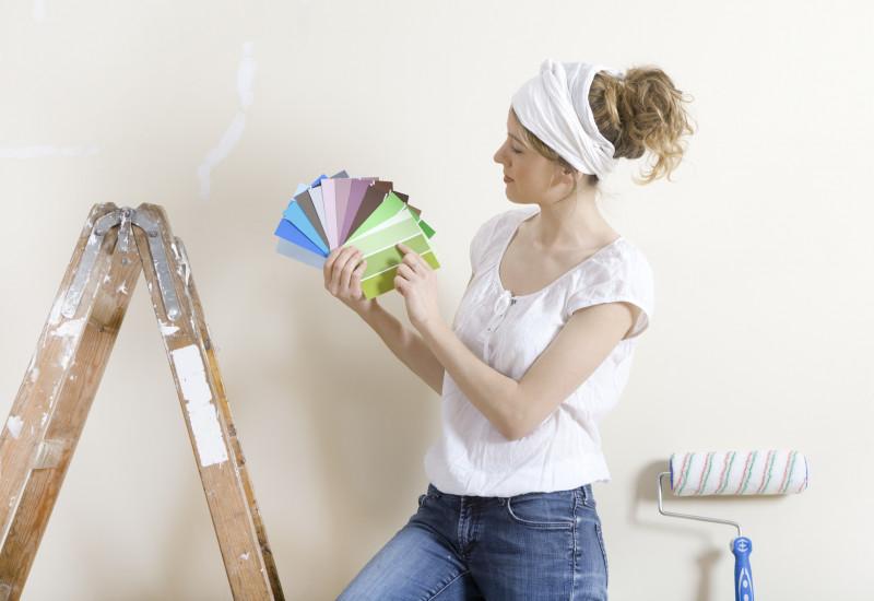 Frau sucht mit einem Farbfächer eine Wandfarbe aus