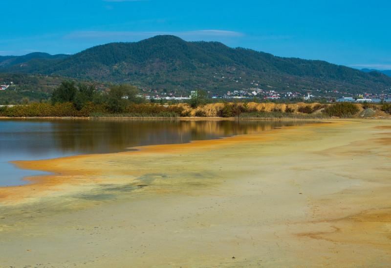 zum Teil wassergefülltes Rückhaltebecken mit naturnahem Ufer, im Hintergrund bewaldete Berge