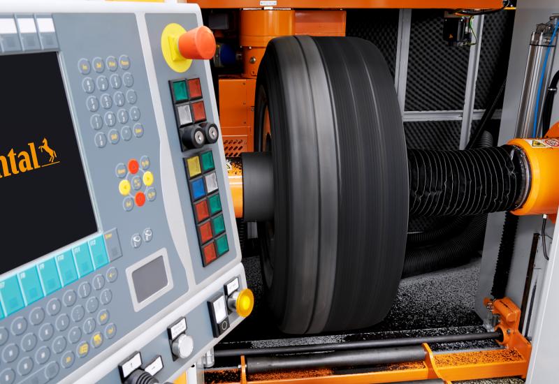 ein Lkw-Reifen ist in eine Maschine eingespannt, daneben ein Bedienpult mit vielen Knöpfen und einem Display