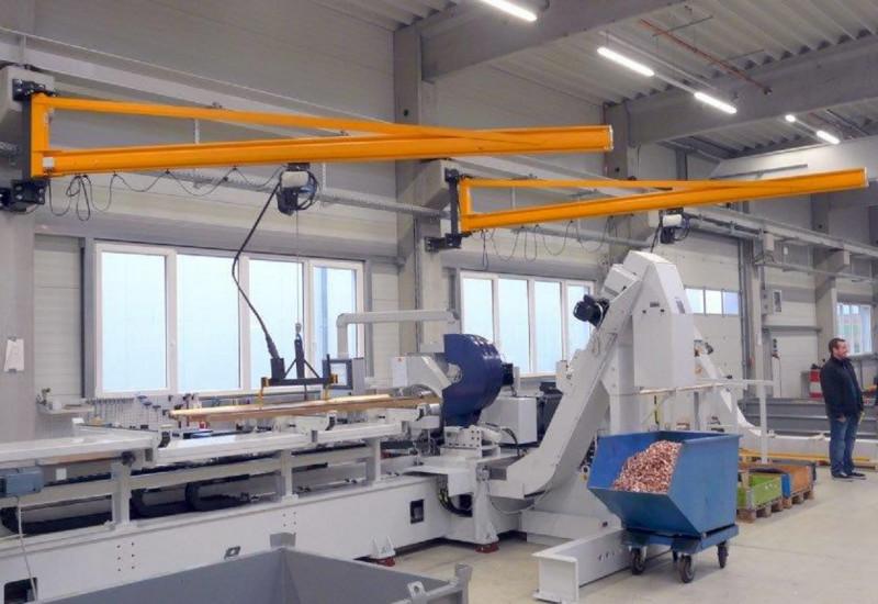 niedrige, aber breite Maschine in einer Werkshalle. Eine Metallstange ist eingespannt, Metallspäne werden in einen Rollcontainer geleitet.
