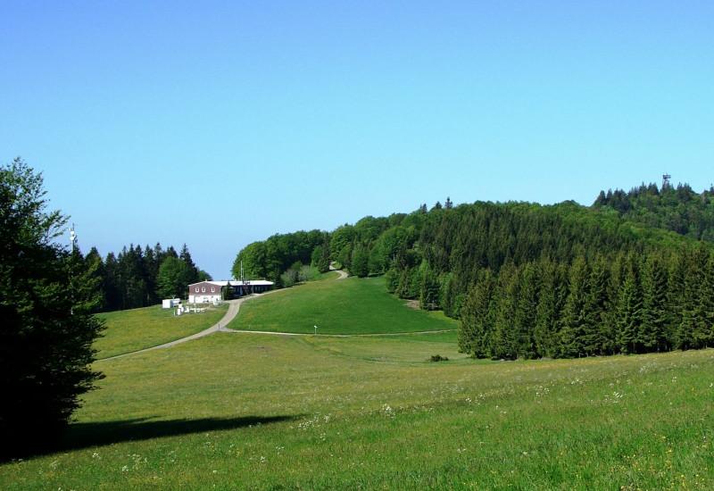 Messstationsgebäude in hügeliger Landschaft mit Wiesen und Fichtenwald