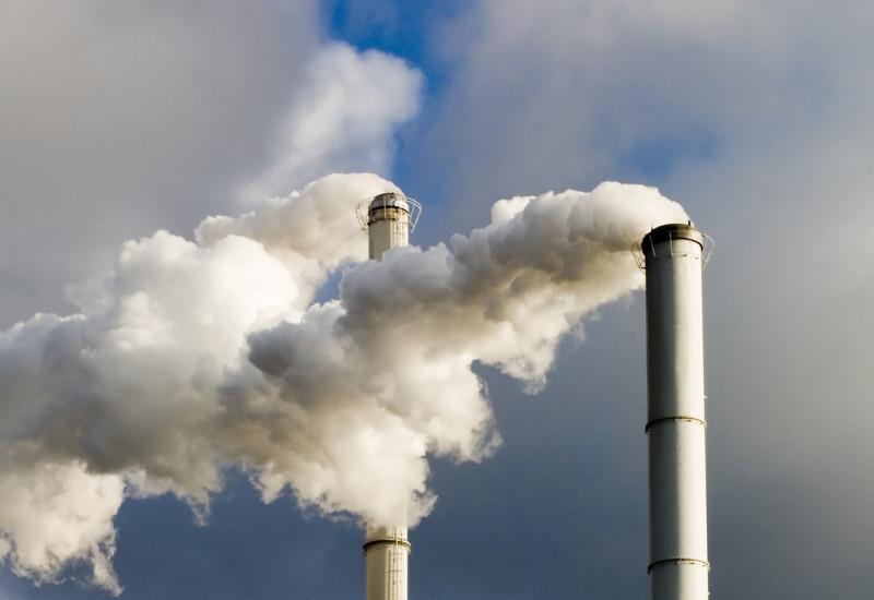 rauchende Schornsteine vor einem bewölkten Himmel