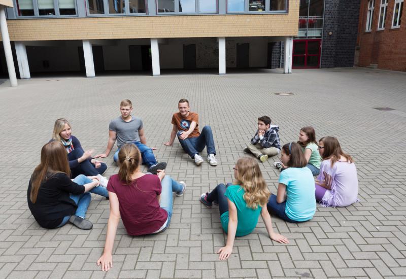 Schüler sitzen im Schulhof, der komplett mit grauen Betonsteinen zugepflastert ist