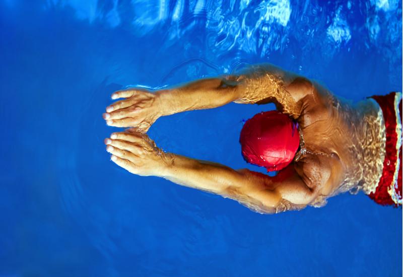 Mann schwimmt in einem Schwimmbecken mit blauem, klaren Wasser. Er trägt eine Badekappe.