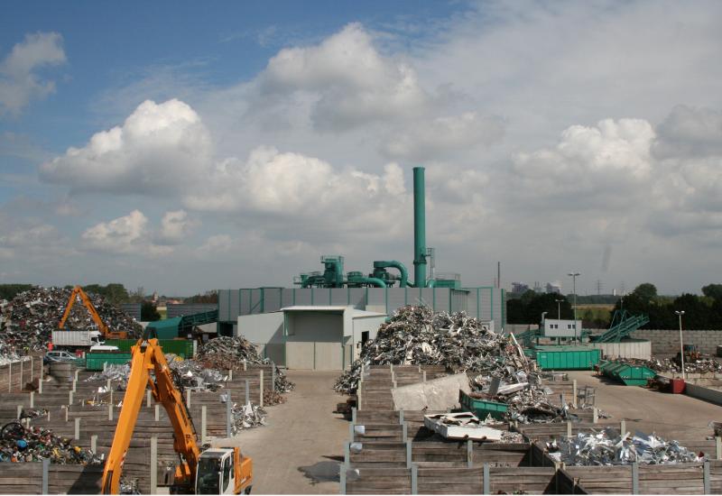 Betriebsanlage mit Metallschrott, auf der Bagger arbeiten, im Hintergrund eine Schredderanlage