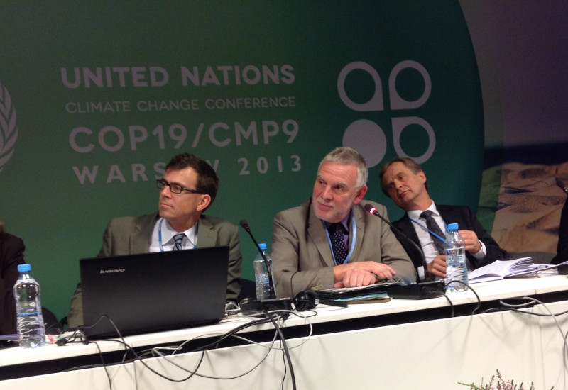 Jochen Flasbarth with other speakers on a podium, in the background the logo of the climate conference in Warsaw