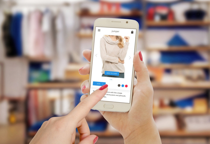 a woman shopping clothes with a smartphone, standing in front of a wardrobe