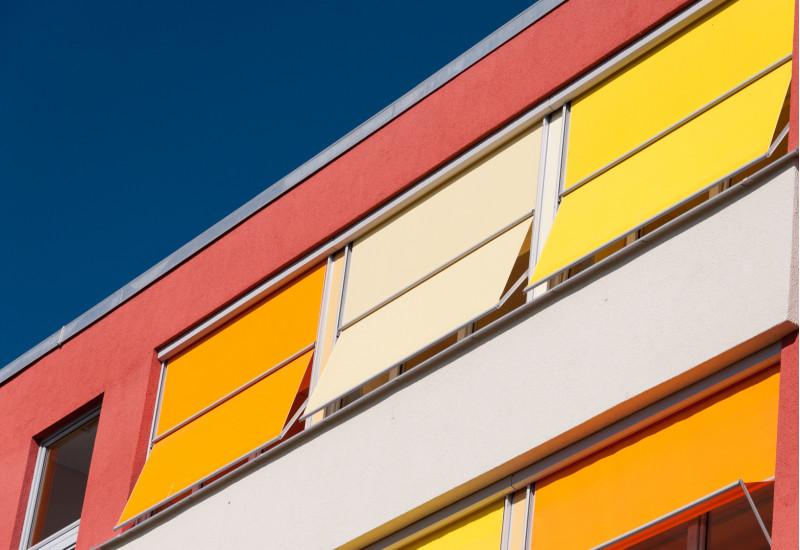 Gebäudefassade mit farbenfrohem Sonnenschutz
