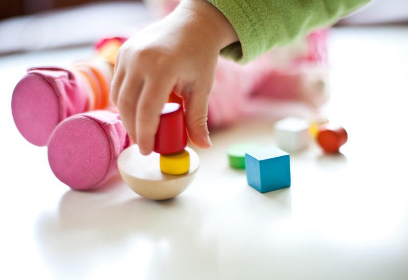 a child´s hand playing with toys