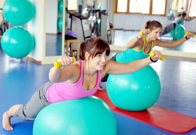 Two women lying on a mat at a sports centre with gymnastic balls and barbells