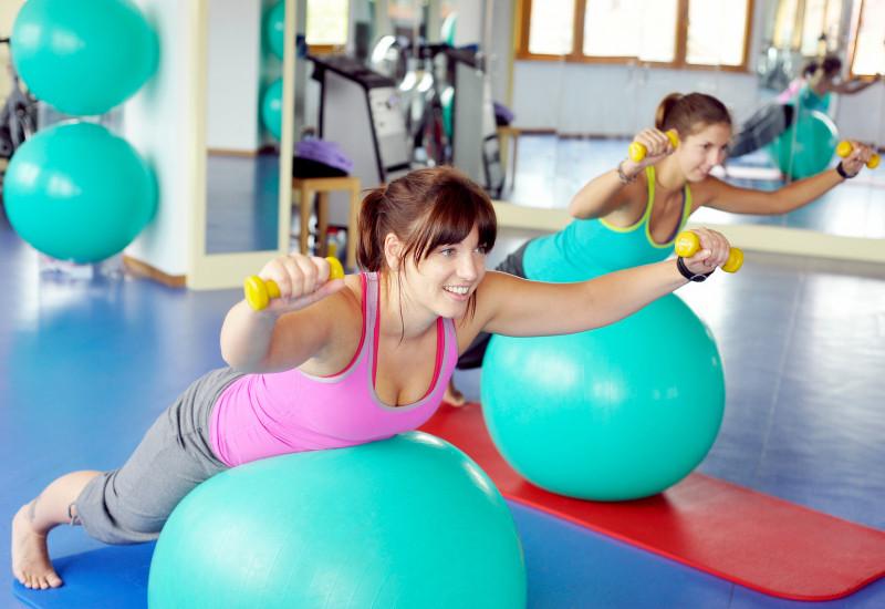 zwei Frauen in einem Sportraum trainieren mit Gymnastikbällen und Hanteln auf einer Matte